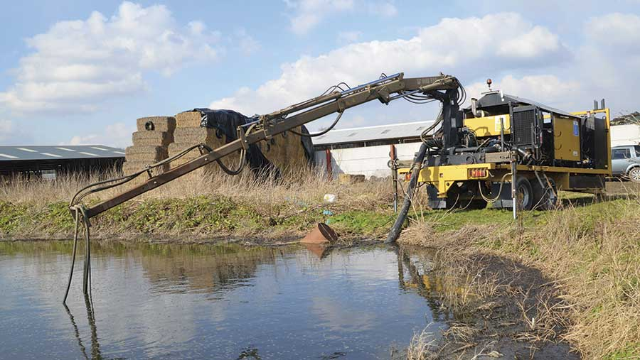 The crane lifts the pump into the lagoon.