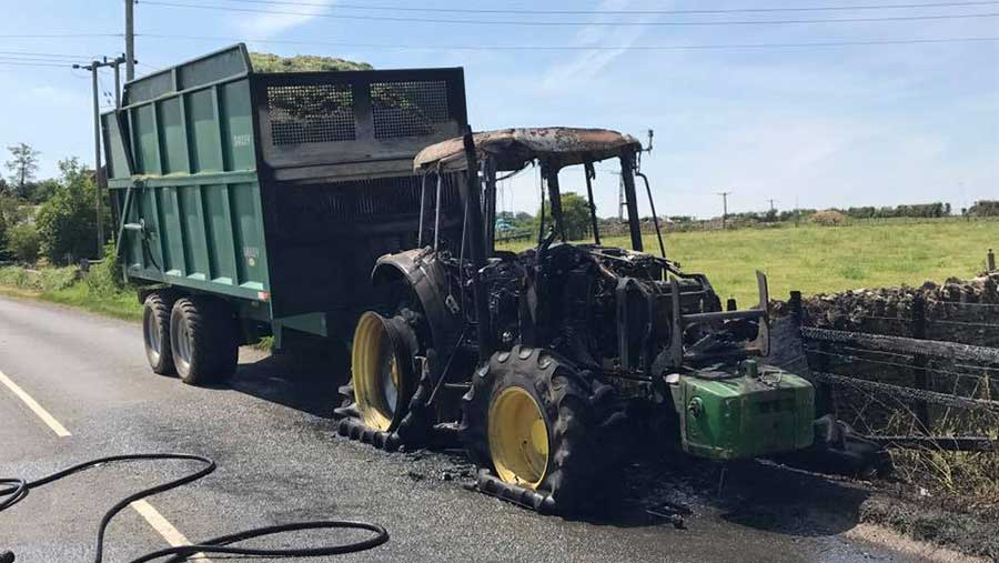 A burned out tractor stands in a road. Behind it is a trailer filled with silage