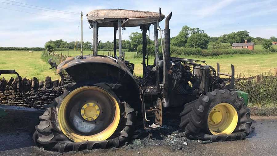 A burned out John Deere tractor stands in the road