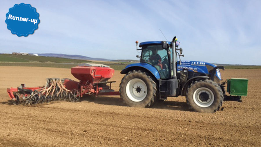 A tractor pulls a drill in a field