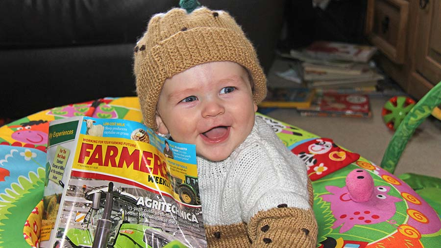 Baby Max dressed as a Christmas pudding reading Farmers Weekly