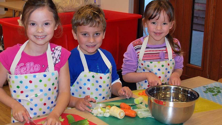 School children preparing vegetables in the farm school's kitchen