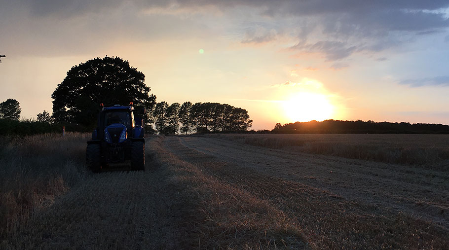A tractor pulling a trailer moves through a field as the sun sets behind it