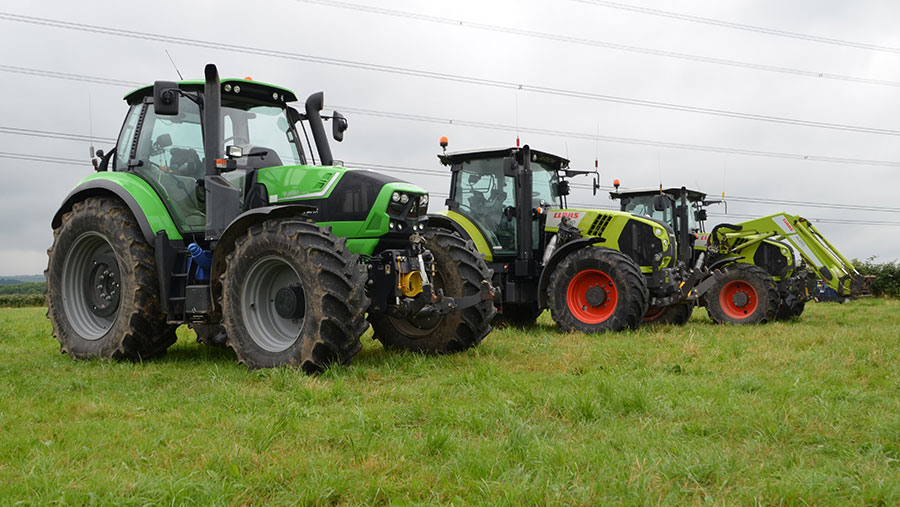 Three tractors stand in a field