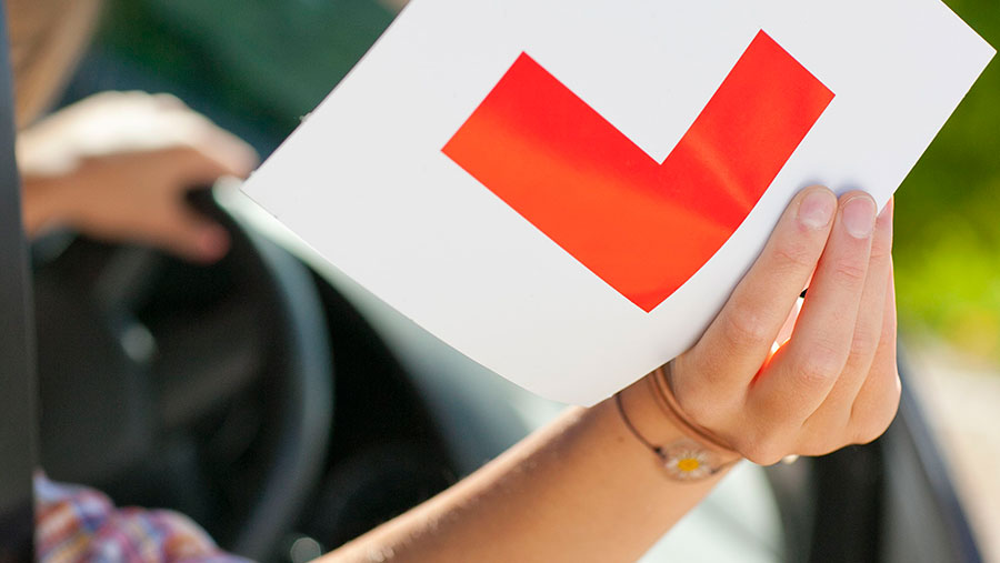 Young woman in car holding up L sticker