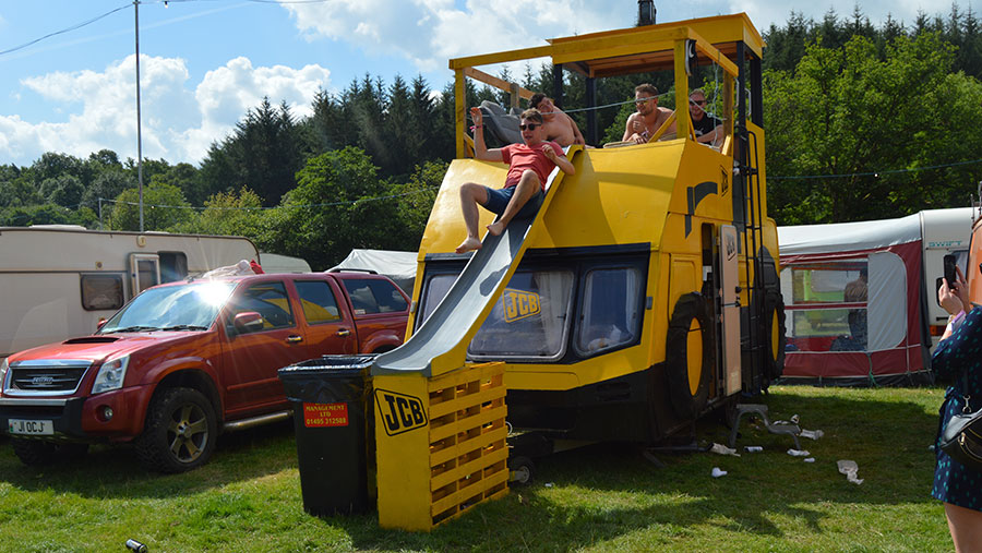 A caravan is decked out in JCB yellow. A rooftop slide has been added. Men watch as one of their group uses the slide