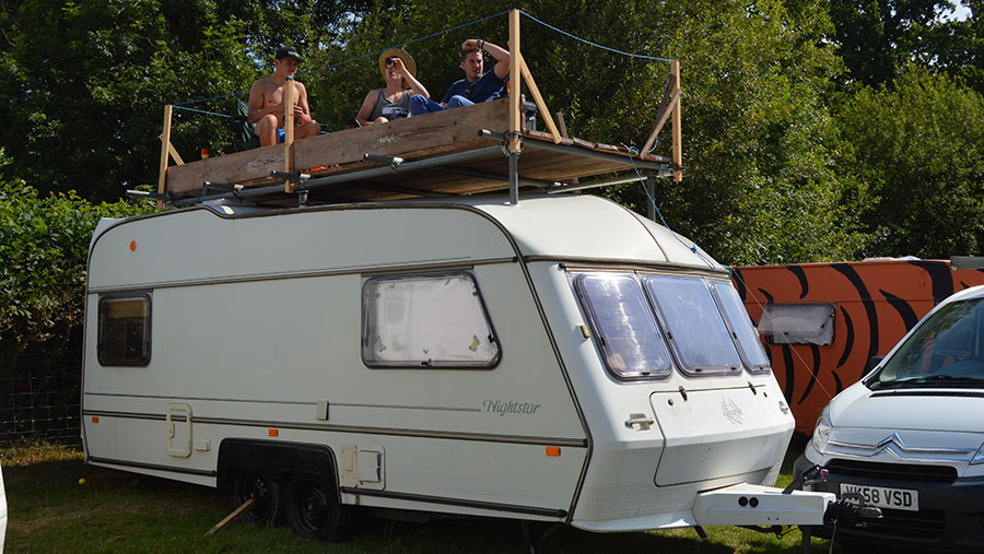 A caravan with a rooftop extension built on top. Sat on the extension are three men