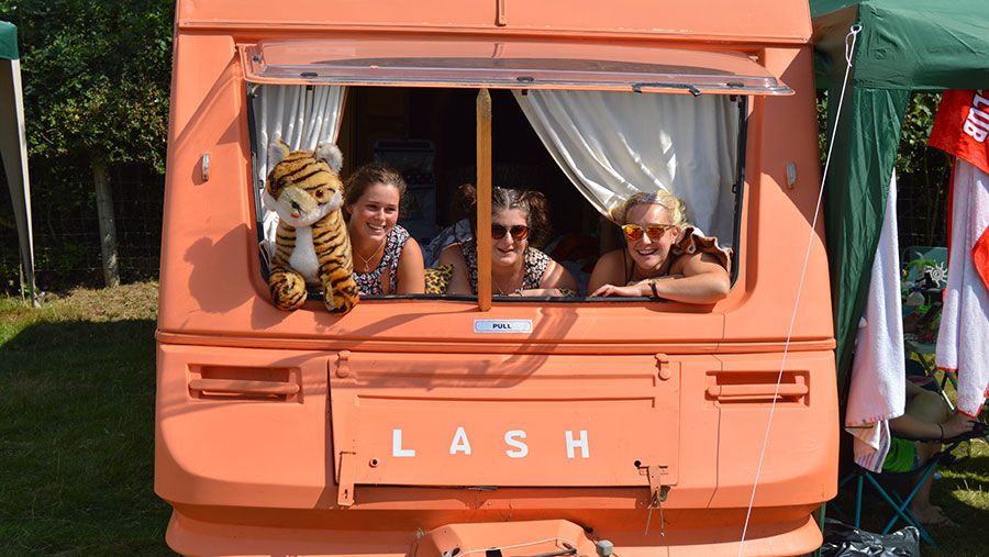 An orange caravan. Three women look out of its window. One holds a toy tiger.