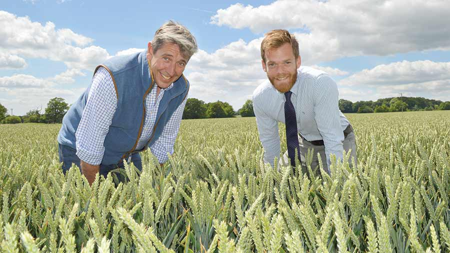 Mark Tubby and Ben Chapman stand in a field of wheat