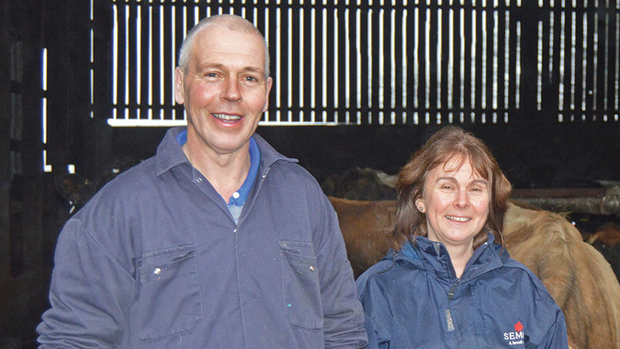 Richard and Heather Gibson stand in a cow shed