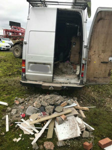 Building rubble sits outside a van with its back door open