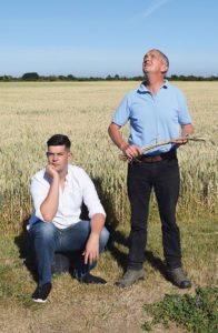 Guy Smith stands looking at the sky why his son, Henry, sits to his left. Both men are in a dry field of wheat