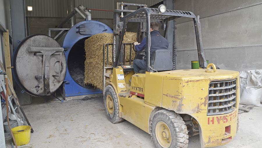 Loading bales into the grain dryer. ©Nick Fone