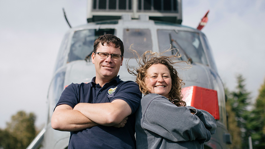 Martyn and Louise Steedman standing in front of Sea King helicopter
