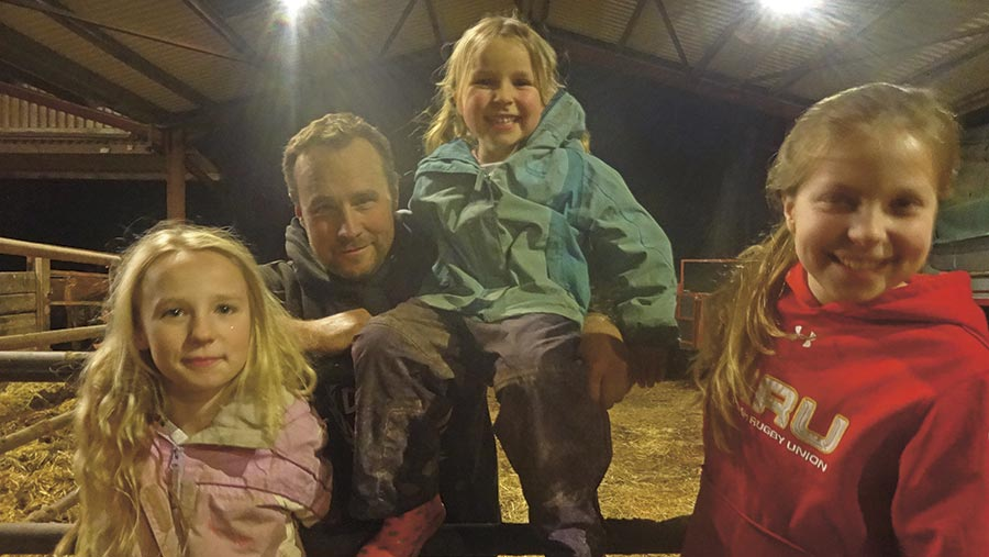 Alan Rees stands in the shed with three children