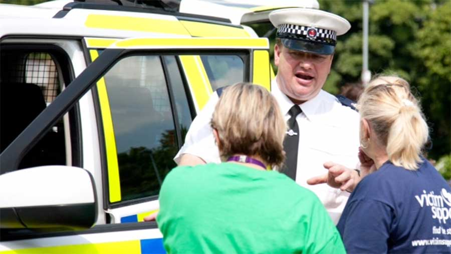 David Slack speaks to two women next to his police car