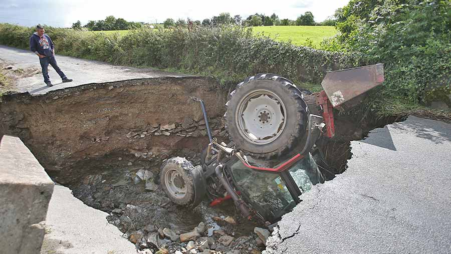 NO REUSE tractor in sinkhole