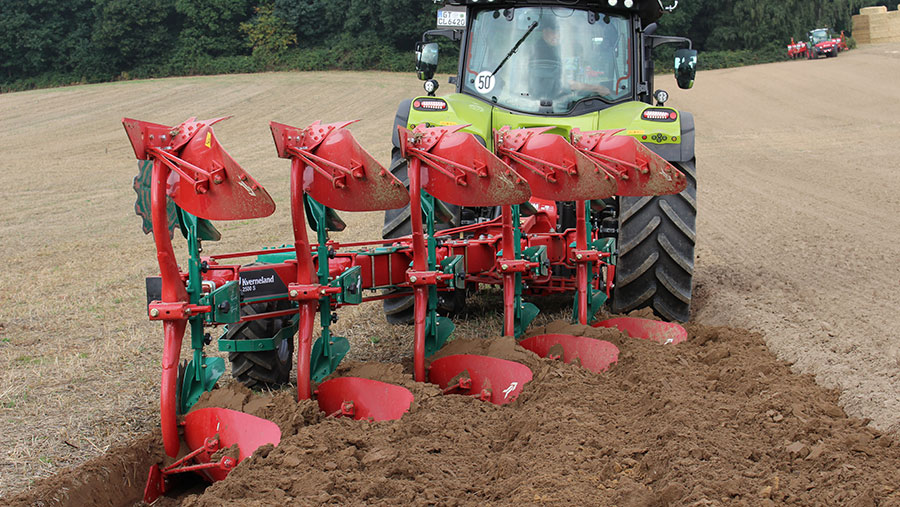 A plough with a midmounted depth wheel works in a field