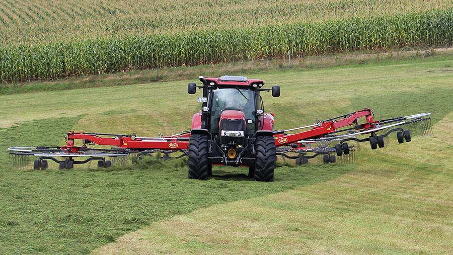 A tractor with a four-rotor rake works in a field