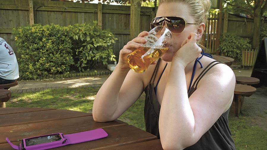 Teenager drinking a beer sitting at a pub