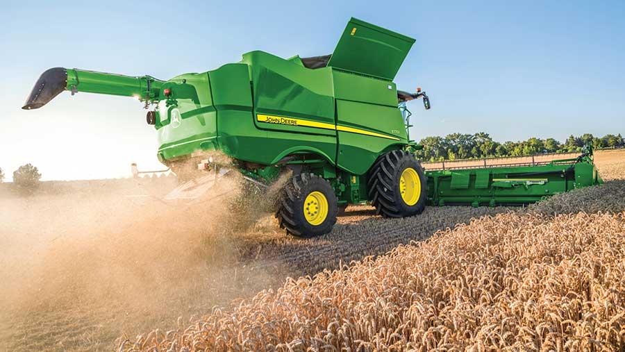 A John Deere S700 combine works in a field