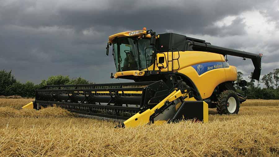 Combine harvesting crop with dark storm louds