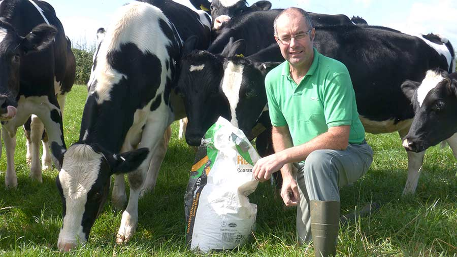 Roger Hildreth kneels in a field with heifers