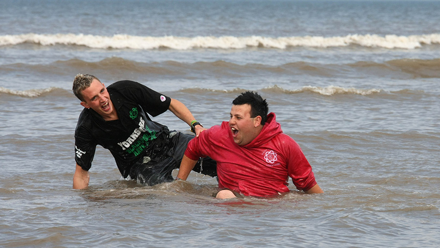 Two young farmers in the sea at Blackpool