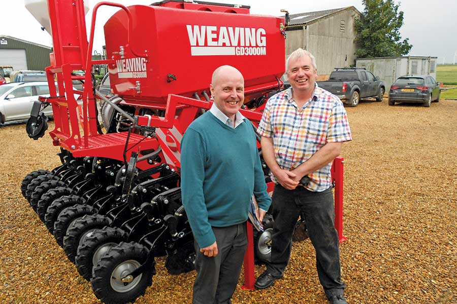 Two farmers stand in front of a seed drill