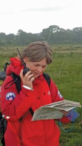Cathy Fairman speaks on a walkie talkie as she looks at a map
