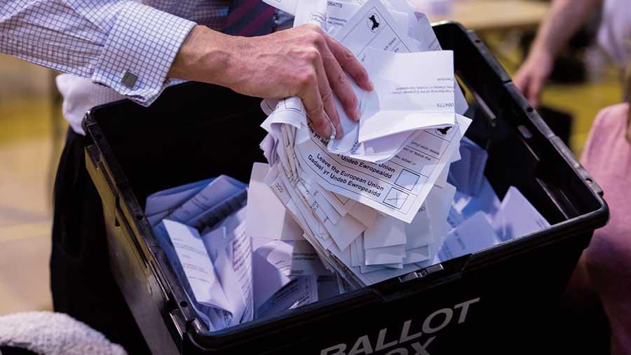 Hand holding EU referendum ballots over ballot box