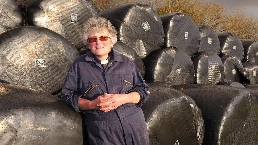 Eileen Davies leaning on silage bales