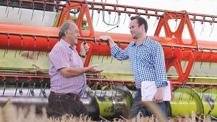 Farmers having a conversation in front of a combine harvester