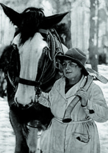 A woman, who is carrying an axe, leads a horse.