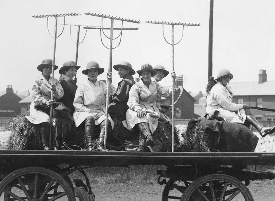 A black-and-white image shows a group of women riding on trailer holding farm kit