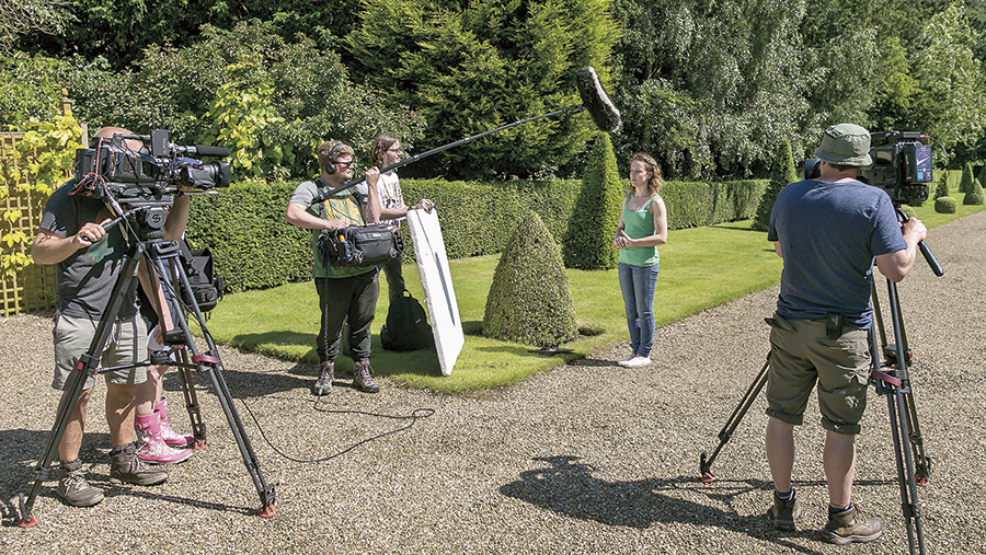 A Farmers Apprentice contestant stands amongst men with cameras