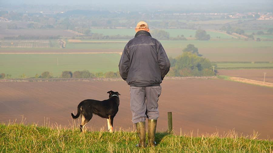 Man and dog standing field