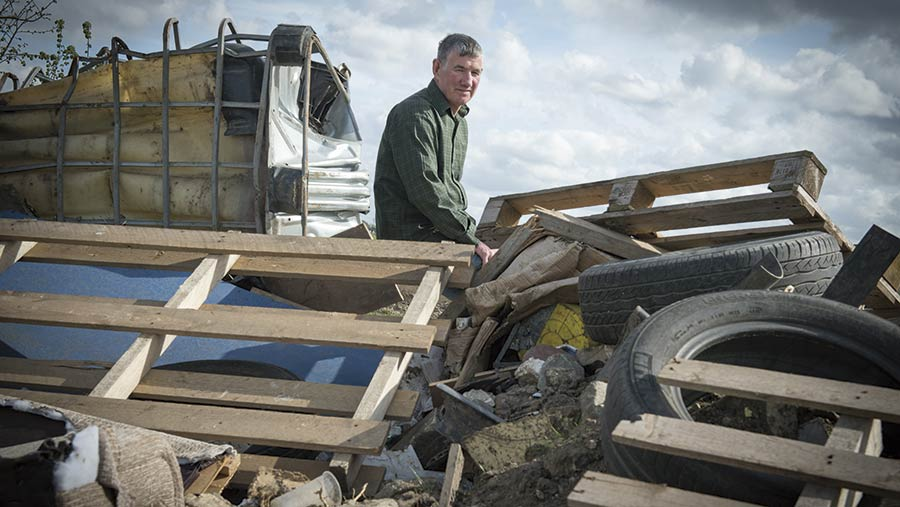 Harry Fisher sits on a pile of fly-tipped rubbish