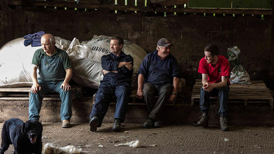 Four farmers sitting in a shed