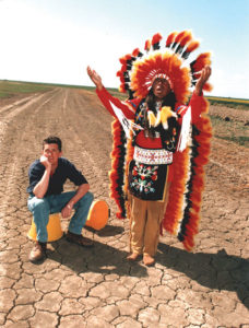 Guy Smith sits to the right of a Native American in a drought-hit field