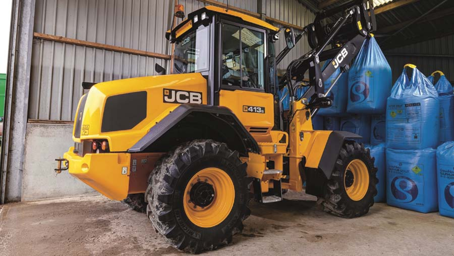 A yellow loader moving large blue bags in a barn