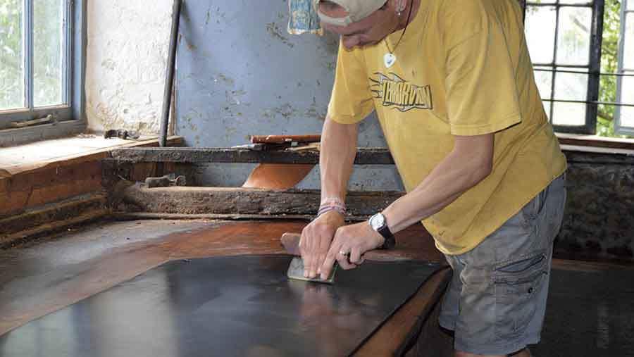 James Tucker polishing a piece of leather