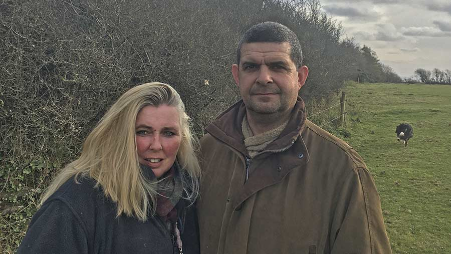 Farmers Jonathan and Alison Andrews standing by a hedge