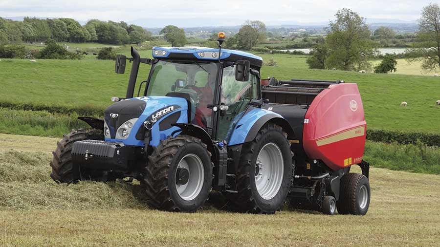 A blue tractor pulling a red baler