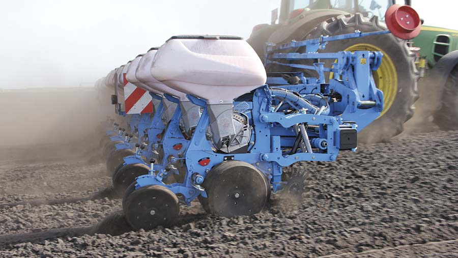 A tractor pulling a blue drill