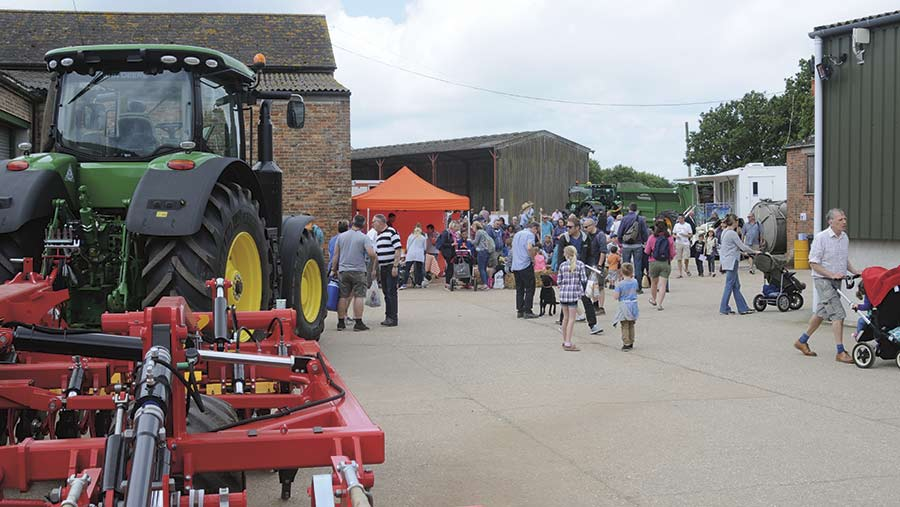 Visitors stand in a farmyard