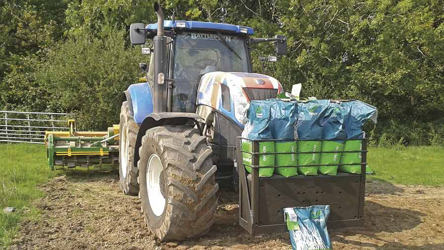 A tractor pulls bags of grass seed