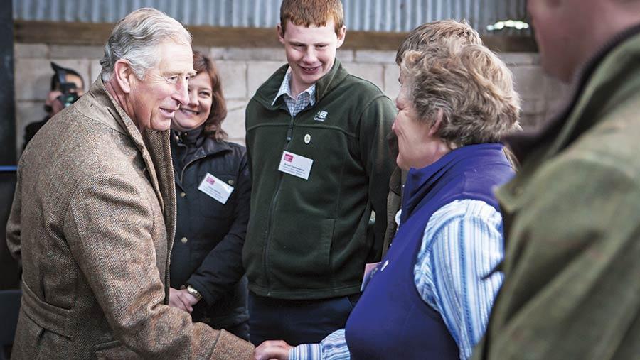 Prince Charles greeting people on a farm