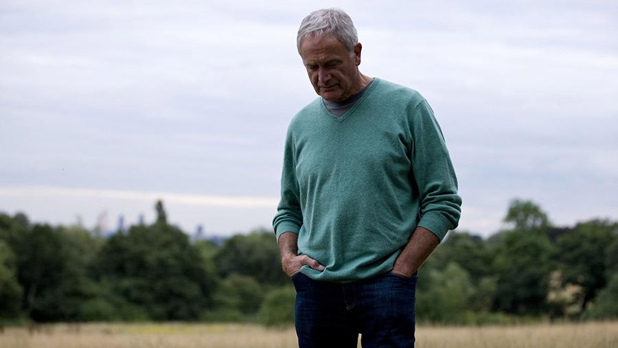 Sad farmer standing in a field