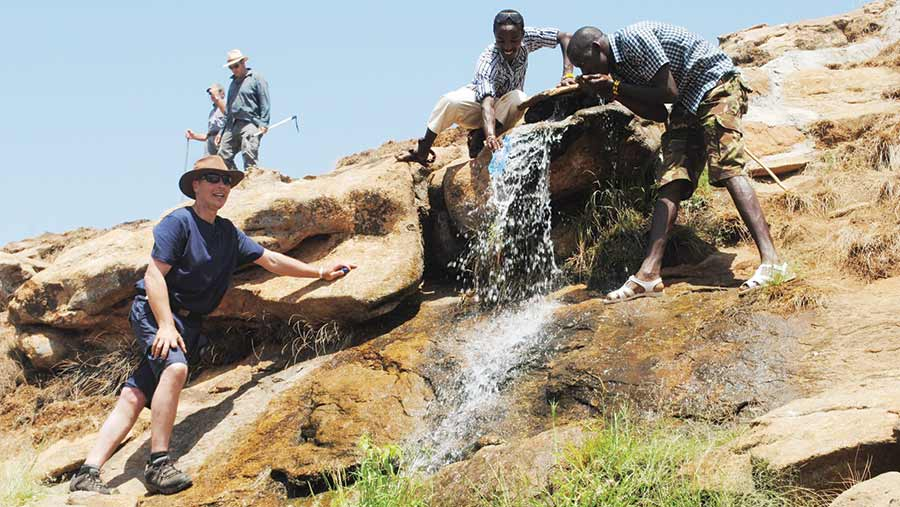 Farmer Richard Gibson stands on a rocky cliff face while two Kenyan men stand to his right next to water rushing down a slope